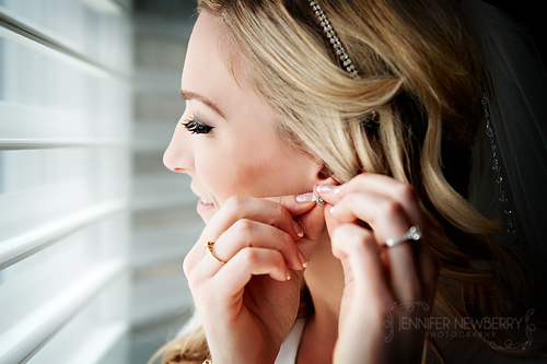 Bride putting earrings on by www.jnphotography.ca @filemanager